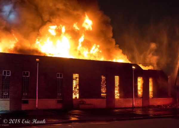 massive fire burns through warehouse roof at night