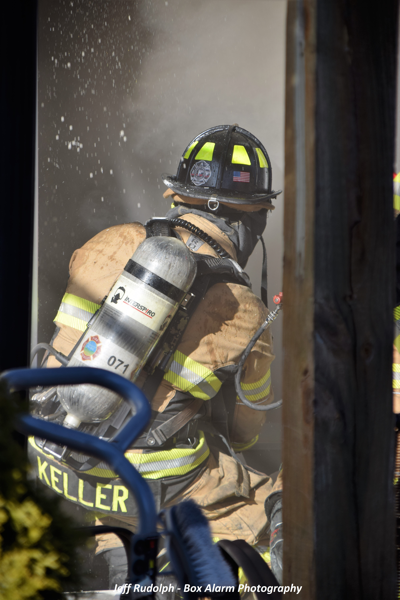 Firefighter uses hose at fire scene