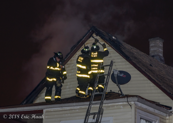 Firefighters work on roof during a house fire