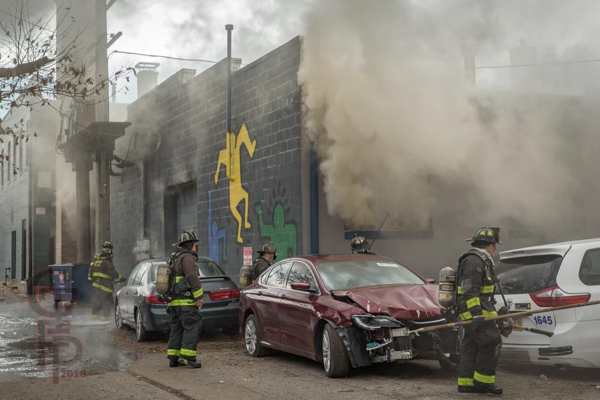 Firefighters at fire scene with heavy smoke
