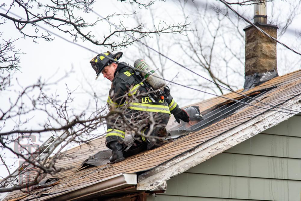 Firefighter on roof of a small house