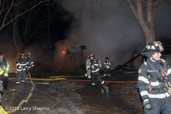 Firefighters at night house fire scene