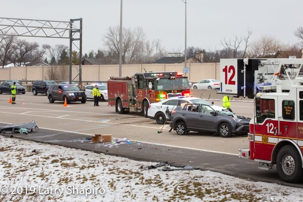 crash scene on highway with fire trucks and police cars