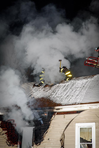Firefighters vent house roof with axes