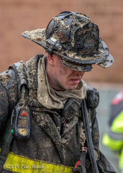 Firefighter covered with insulation after overhauling a fire