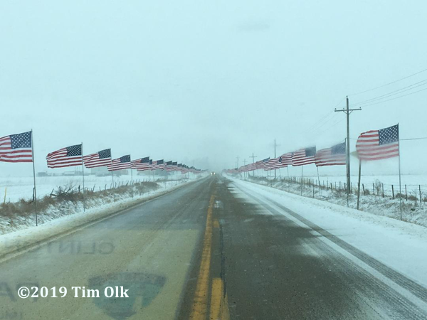 American flags line road for Firefighter funeral