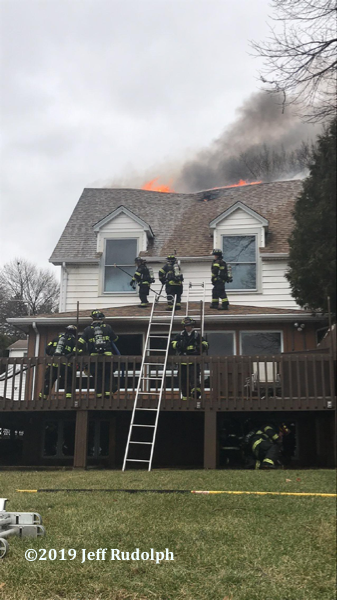 Firefighters battle fire in a large house with flames through the roof