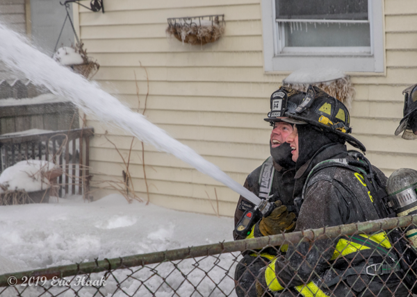 Firefighters with hose line in the winter