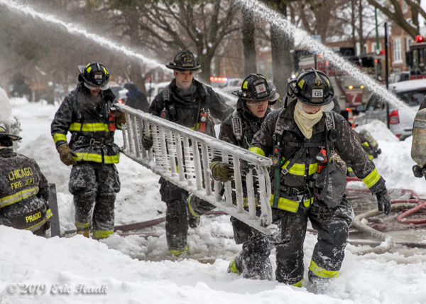 Firefighters carry ladder covered with ice at winter fire scene