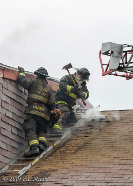 Firefighters vent roof wth axe