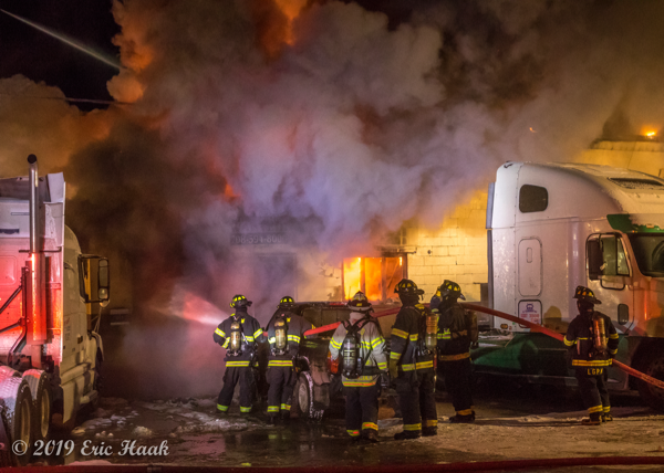 Firefighters battle fire in a truck repair shop