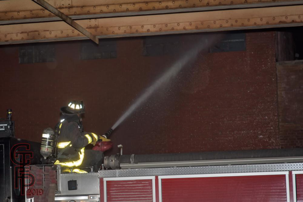 Firefighter operates deck gun on engine at fire scene