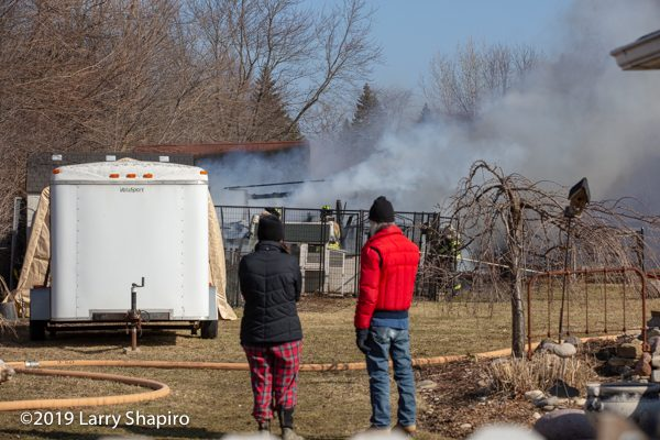 residents watch shed fire in back yard