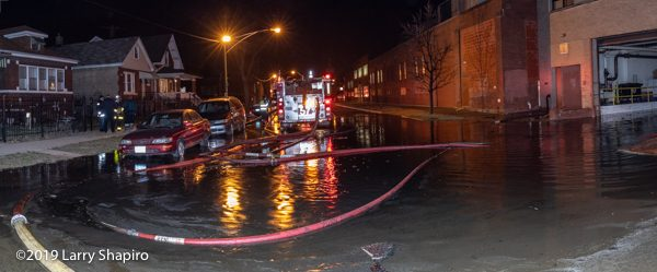 flooded street at scene of massive fire