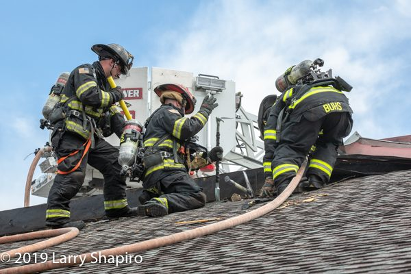 Firefighters vent commercial building roof