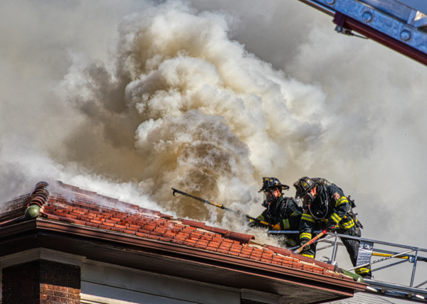 dramatic photo of Cicero Firefighters venting a roof in heavy smoke from aerial ladder
