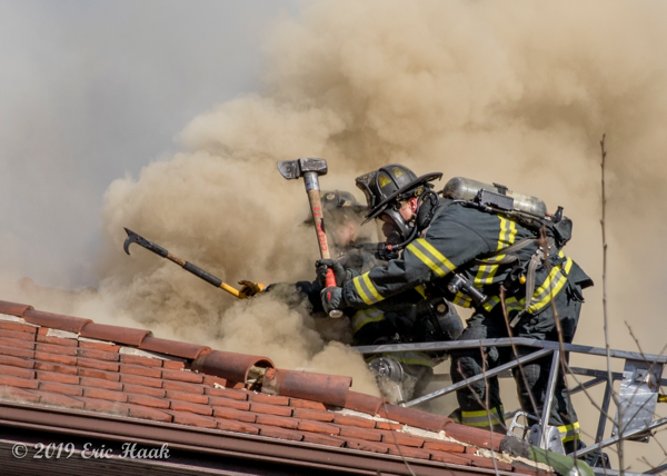 dramatic photo of Firefighters venting a roof in heavy smoke from aerial ladder