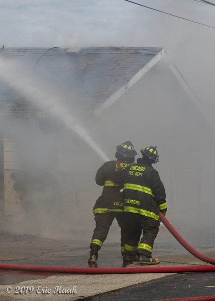 Firefighters advance on fire with hose line