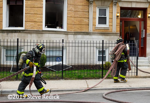 Firefighters carry hose at a fire