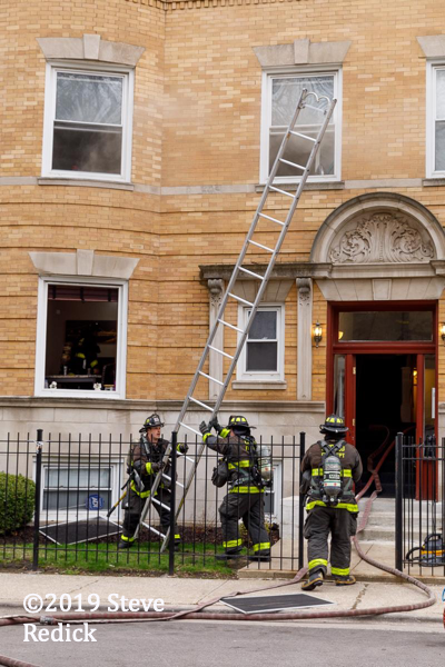 Firefighters raise ground ladder at fire