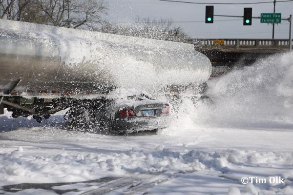 foam applied to car wedged under a gasoline tanker