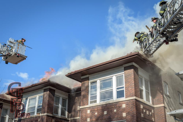 Firefighters vent roof of apartment building on fire