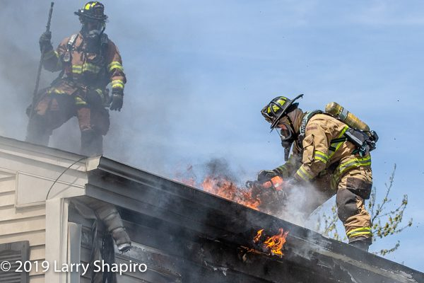 Firefighters vent roof of building with smoke and fire