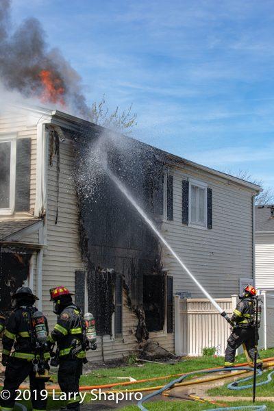Firefighter with hose line battles fire