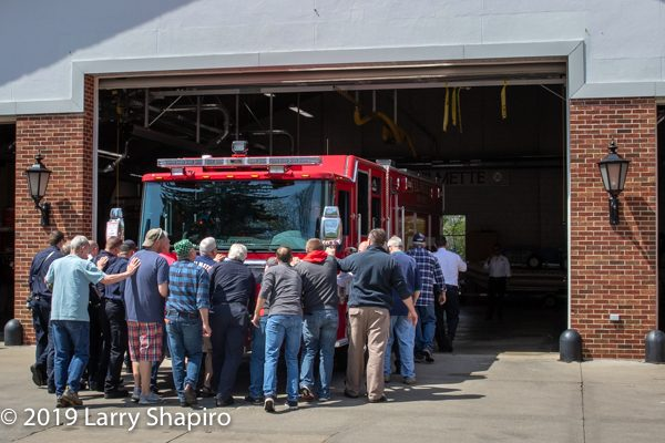 active and retired firefighters push new fire engine into the station