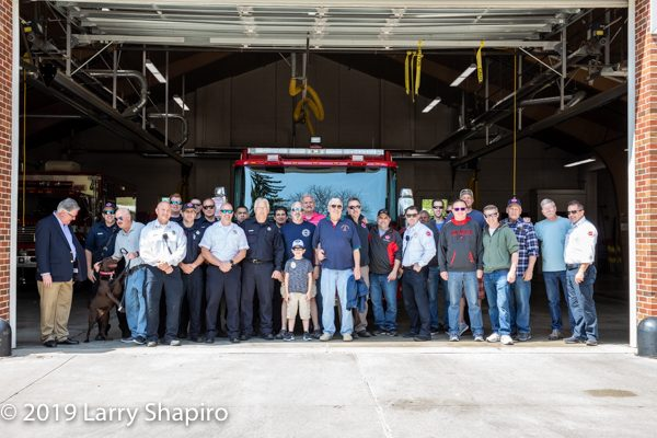 active and retired firefighters pose with new fire engine