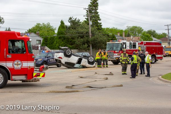 Firefighters at a crash site with an SUV rolled over on the roof