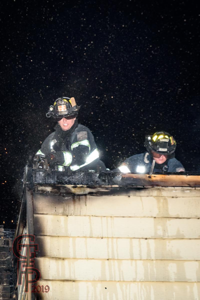 Firefighters on roof of building fire at night