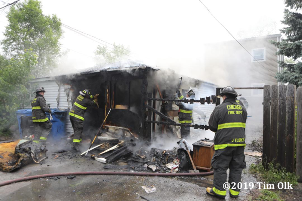 Firefighters overhaul after an alley garage burned in Chicago