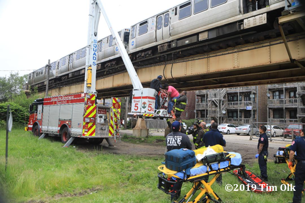 Chicago Firefighters remove civilians from an elevated train derailment