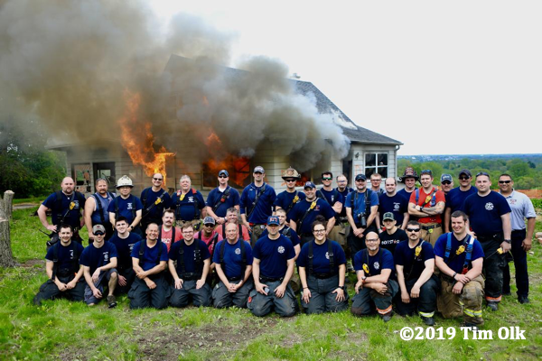 Firefighters pose in front of burning house