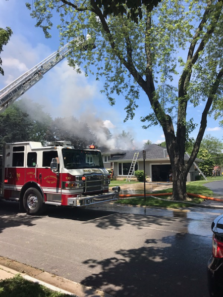 fire and smoke through the roof of a house on fire
