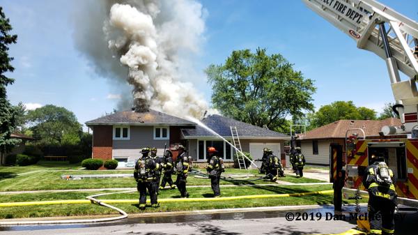 Firefighters battle house on fire