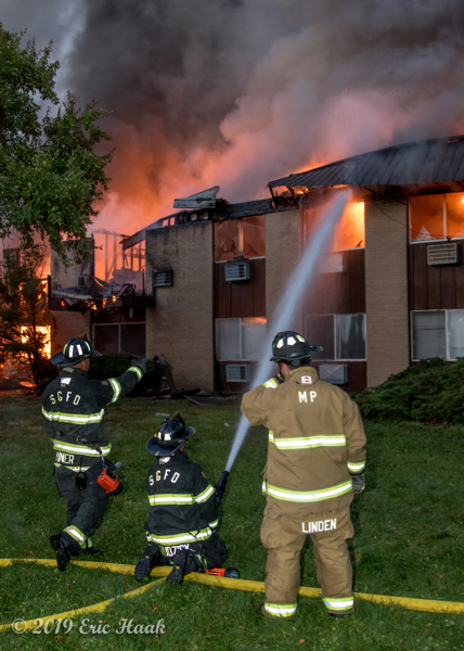 Firefighters battle apartment building fire at night