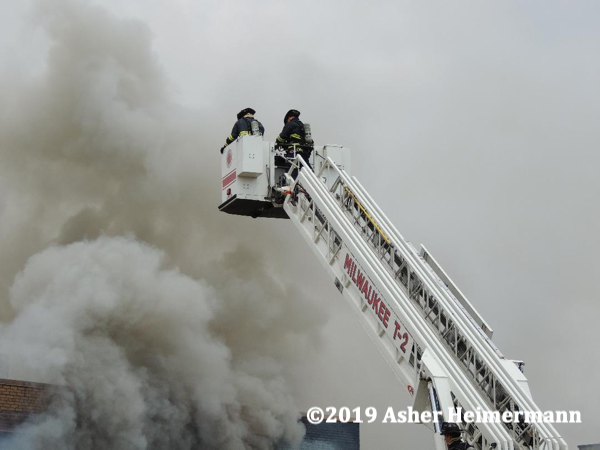 Firefighters in tower ladder basket battling a fire