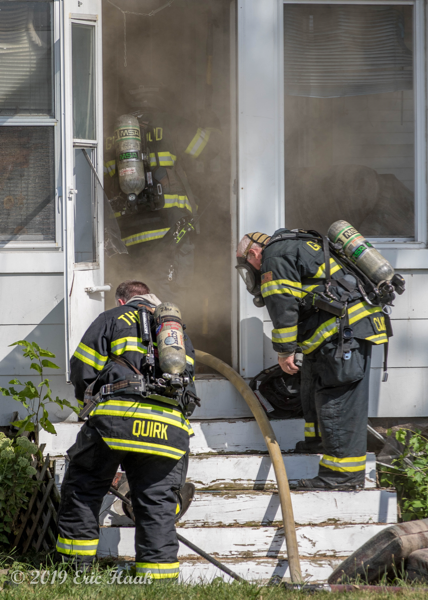 Firefighters put on SCBA before entering smokey house fire