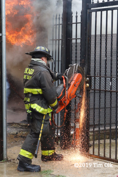 Firefighter uses saw to cut metal fence