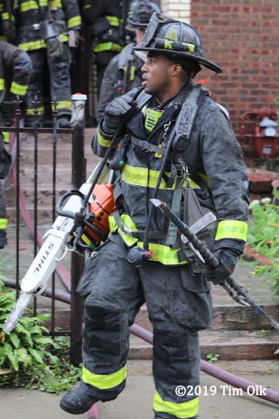 African American Firefighter with PPE carrying tools