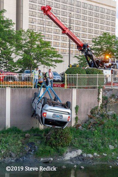 tow truck lifts upside down car from a creek