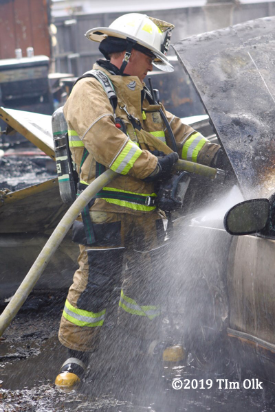 firefighter extinguishes a car fire