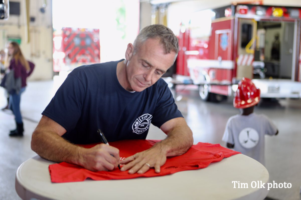 Actor from Chicago Fire tv show signing a shirt