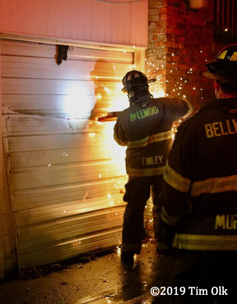 Firefighters cut metal door at fire