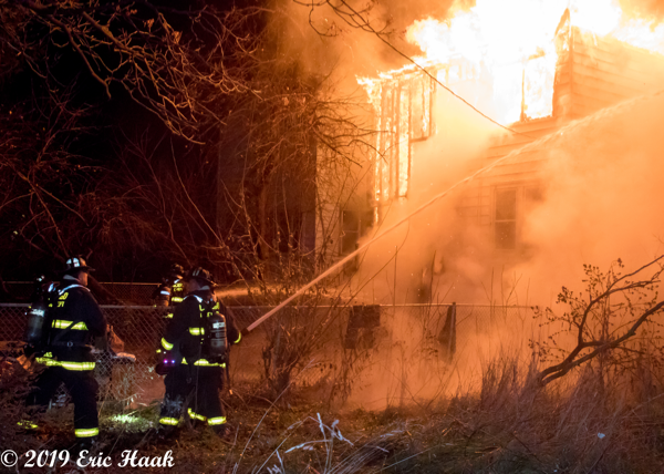 Firefighters battle flames at night