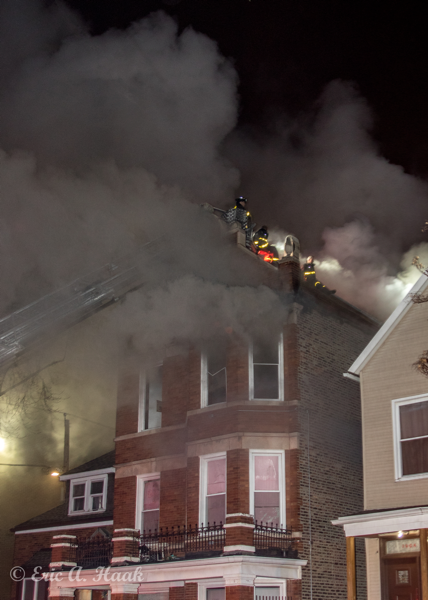 Firefighters on roof in heavy smoke
