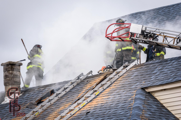 Firefighters vent roof during a fire
