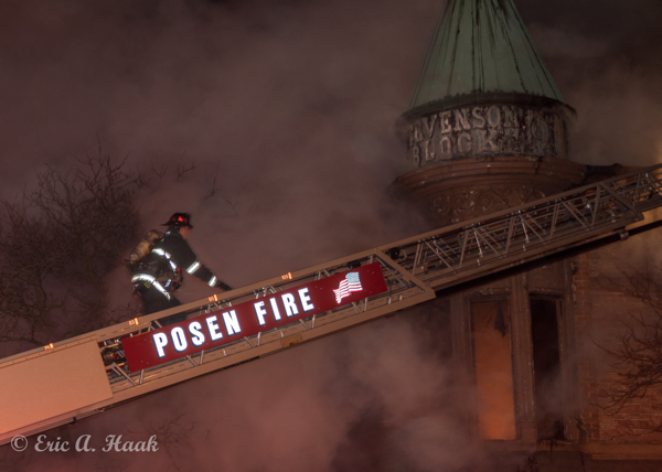 Firefighters climb aerial ladder at night